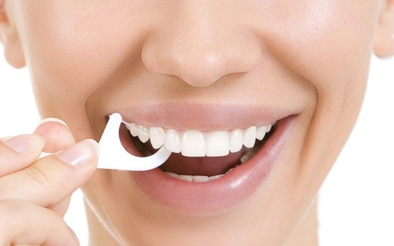 Dùng chỉ nha khoa để loại bỏ thức ăn thừa trong kẽ răng